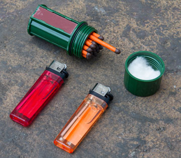 Components from the Ultimate Urban Survival Kit, including Emergency Matches and BIC lighters on brown background