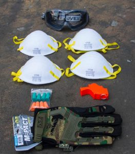 Items from the Ultimate Urban Survival Kit - Mechanix Gloves and Uvex Goggles on brown background