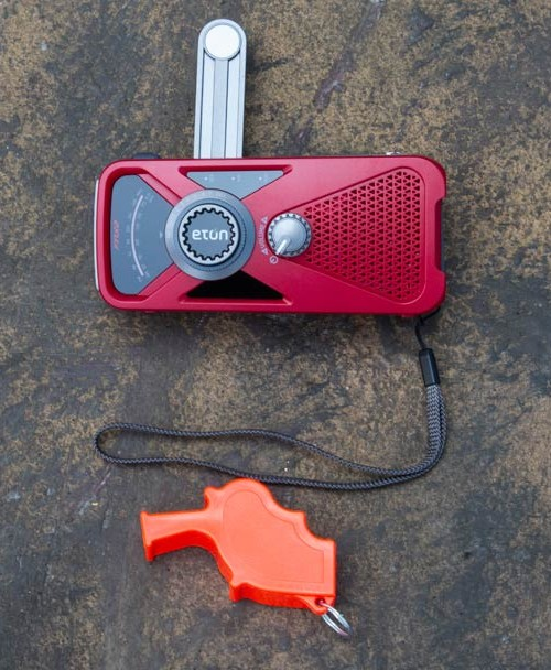 ETON FRX2 Radio and Storm Whistle on brown background