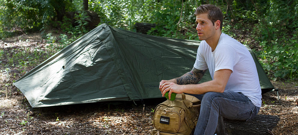 Man sitting in the forest with a one person tent and his bug out bag